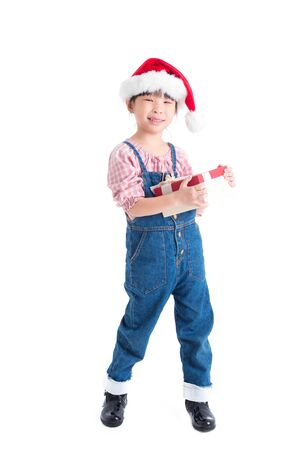 Full length of little asian girl wearing santa claus hat holding gift box and smiles over white background Stock Photo