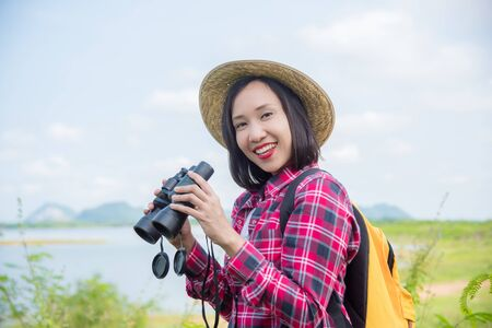 Beautiful Asian woman using binoculars to see the birds between trekking in the forest.