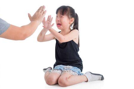 Triste fille asiatique pleurant pendant que sa mère la punit sur fond blanc, concept de maltraitance des enfants. Banque d'images