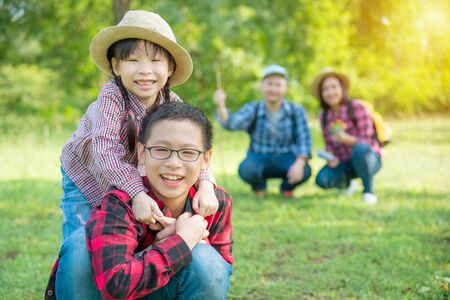 Happy asian siblings smiling with their father and mother sitting in background. Stock Photo - 137358108