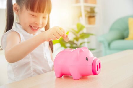 Little asian girl inserting coin into pink piggy bank and smiles,focus on coin and girl's hand.