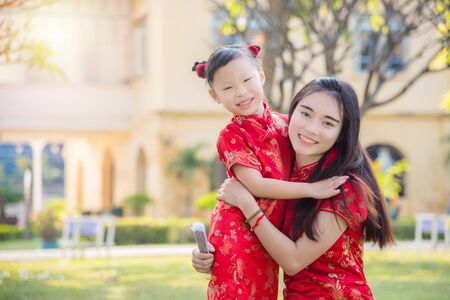 Beautiful mother and her daughter in chinese traditional dress (cheongsam) smiling in garden. Standard-Bild - 133948261