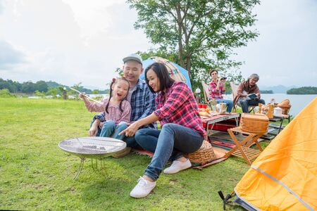 Happy asian family sitting together in front of tent at campping site. Stock Photo - 137357831