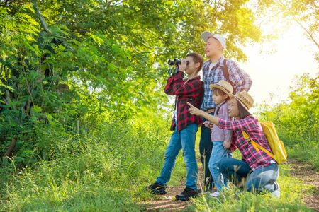 Happy asian family trekking in forest together on vacation. Stock Photo - 137356651