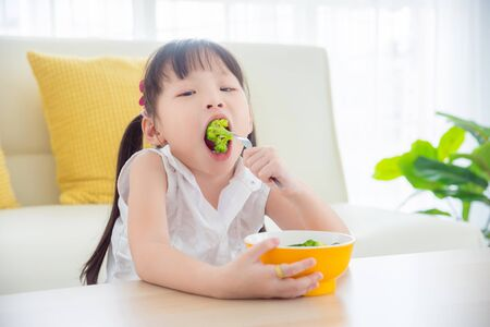 Little asian girl eating broccoli at home,Healthy food for child concept. Stock Photo