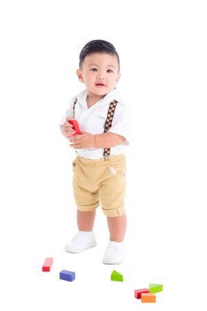 Little asian male toddler standing and smiles over white background 版權商用圖片