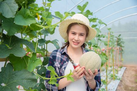 Beautiful asian farmer holding fresh melon that cultivated from her organic farm and smiles.