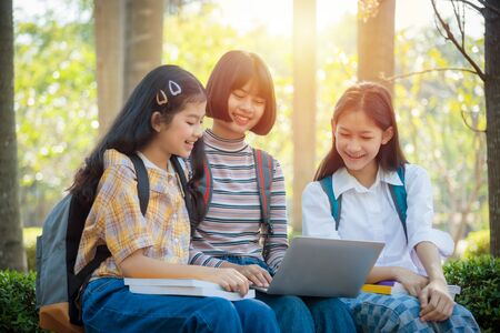 Three asian teenager student sitting in park and using notebook computer for doing homework together Imagens