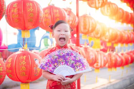 Little asian girl wearing chinese treditional costume standing with red lantern and smiling in chinese new year festival. 版權商用圖片