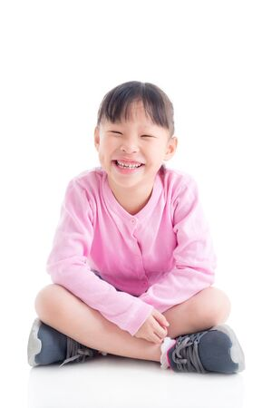 Happy little asian girl sitting and smiling over white background Stock fotó