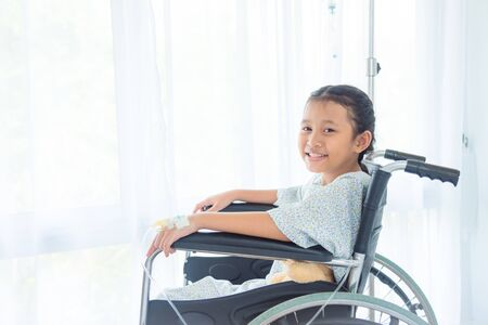 Asian sick girl with intravenous set on left hand sitting on wheel chair and smiles at hospital.