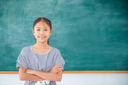 Young asian female student standing and smiles in front of green chalkboard background.