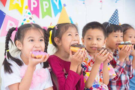 Group of asian children eating donut together at birthday party.