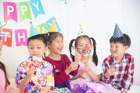 Group of asian children sitting on sofa ,holding party accessory and smile at birthday party.