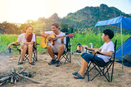 Young Asian family singing with guitar at camping site, father and mother with a son camping in a tent outdoors.
