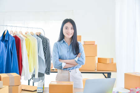 Female startup small business owner standing with crossed arm and smiles at camera. Online selling. E-commerce. Standard-Bild