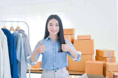 Female startup small business owner standing with smiles and showing thumbs up at camera. Online selling. E-commerce.