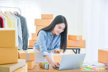 Female startup small business owner working with notebook computer at office. Online selling. E-commerce.