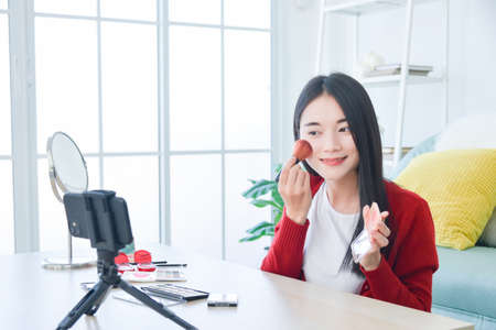 Young asian female blogger recording cosmetic makeup tutorial