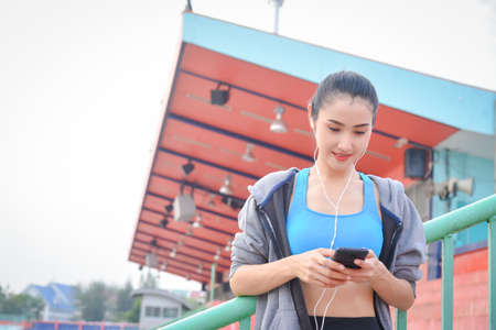 Beautiful asian woman in sportswear listening to music on earphones after exercising outdoors in the city. Standard-Bild