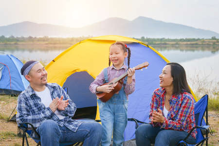 Happy little asian girl playing ukulele and her parents clapping hands at camping site. Standard-Bild