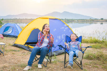 Asian mother and little daughter having fun camping , sitting in front of tent and blowing soap bubbles . Family activity outdoor concept.
