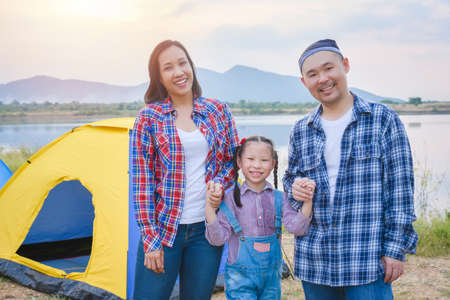 Group of asian family travel and camping at lakeside in forest ,standing all together and smile. Family and outdoor activity concept.