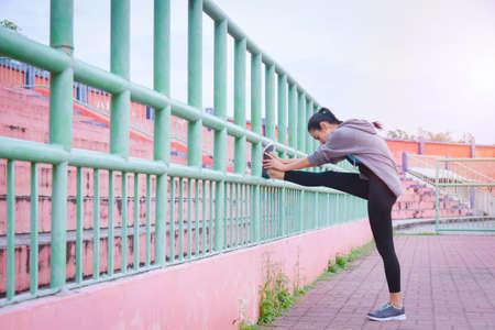Beautiful asian woman in sportswear stretching before run outdoors in the city. Standard-Bild