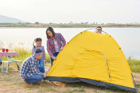 Asian parent with children setting tent by the lake. Family outdoor activity adventure on vacation. Standard-Bild