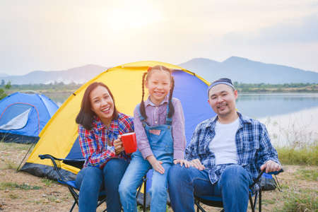 Group of asian family travel and camping at lakeside in forest ,sitting all together and smile. Family and outdoor activity concept.