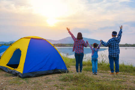 Back view of asian family watching sunset in the evening at camping site by the lake. Family activity adventure on vacation. Standard-Bild