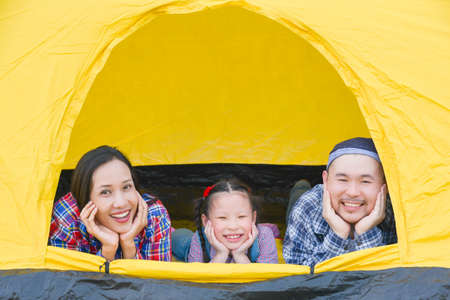 Happy asian family camping on vacation .Father, mother and daughter lying together in tent and smile.