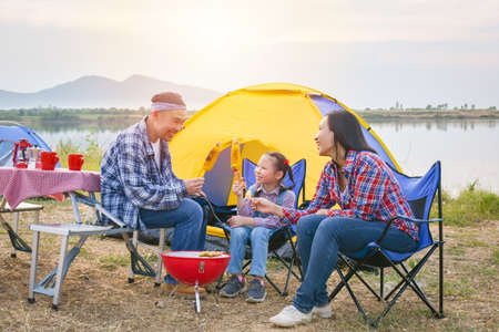 Group of asian family grilling sweet corn and BBQ on stove at camping site, everyone feeling happy. Family outdoor activity concept. Standard-Bild