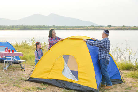 Asian parent with daughter setting tent by the lake. Family outdoor activity adventure on vacation.