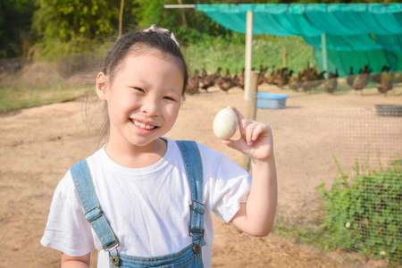 Little asian girl showing duck egg from her farm and smiles.