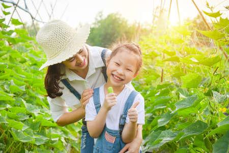 Little asian girl eating fresh cucumber from her garden and smiles.