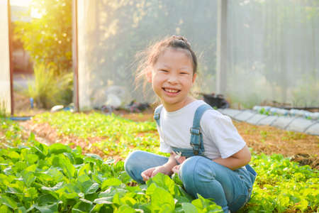 Little asian girl sitting and smiling in greenhouse.
