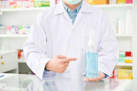 Pharmacist holding alcohol gel bottle and pointing to it at drugstore. Standard-Bild