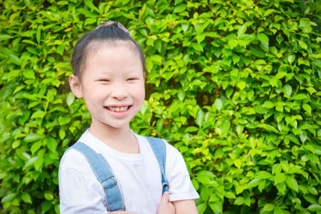 Little asian girl toothly smiles with green leave wall on background.