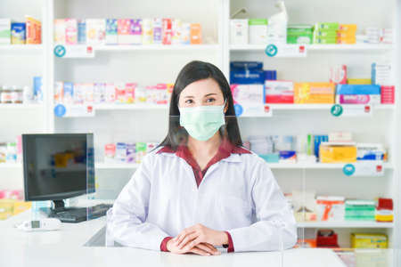 Asian professional young pharmacist wearing face mask while standing behind partition at drugstore.