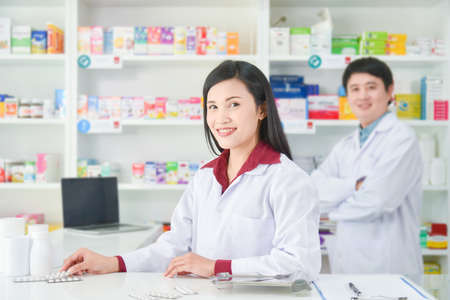 Asian professional young pharmacists standing with smile at drugstore.