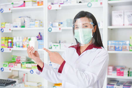 Asian professional young pharmacist wearing faceshield and mask while medication explain at drugstore.