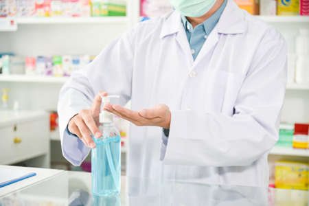 Pharmacist pumping alcohol gel from bottle for washing hand at drugstore.