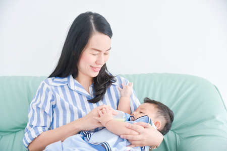 Beautiful asian mother feeding milk her son on sofa at home.