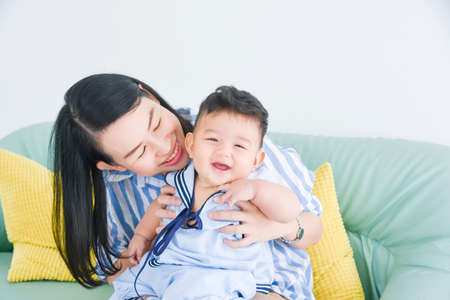 Beautiful asian mother playing with her little son on sofa at home. Standard-Bild