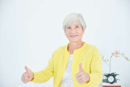 Female asian elderly with white hair smiling and showing thumb up at camera. Healthy senior concept.