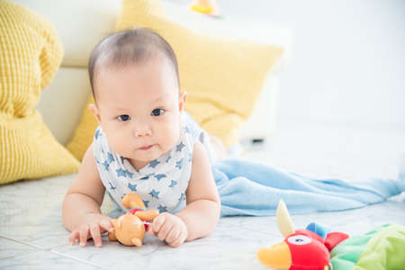 Little asian cute boy laying on the floor and looking at camera.