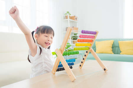 Pretty asian girl playing wood abacus at home. Child education concept.