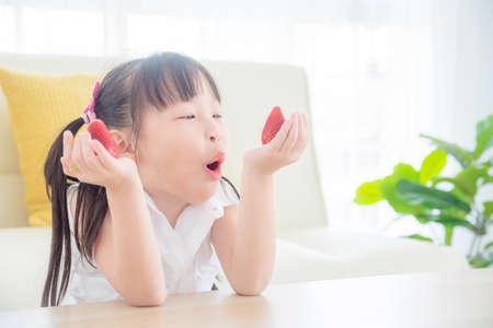 Pretty little asian girl eating strawberry at home. Healthy food and kid concept.