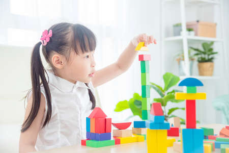 Pretty asian little girl playing colorful wood blocks at home. Child education concept. Standard-Bild